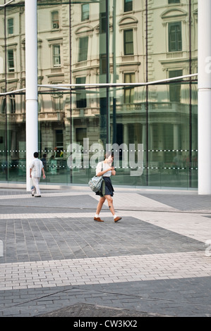 Young woman walking in front of Imperial College, Exhibition Road, South Kensington, London, UK - Stock Photo