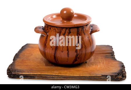 Dirty ceramic pot on old kitchen board. Isolated on white background - Stock Photo