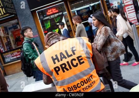 Man wearing a hi vis jacket with Half Price written on it, discounts, London - Stock Photo