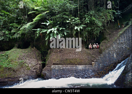 Three men squatting at a water irrigation dam used by a Subak while local villagers look on. - Stock Photo