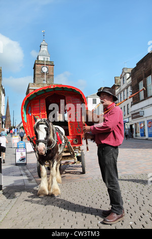 Man playing pipes in front of Gypsy style horse drawn caravan at Dumfries, Scotland, UK - Stock Photo