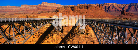 This Navajo Bridge that crosses Colorado River. In background are Vermillion Cliffs Red Rock. This double bridge - Stock Photo