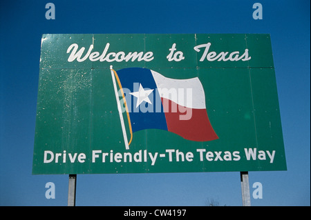 This road sign that says Welcome to Texas drive friendly Texas way. It against blue sky with he Texas state flag - Stock Photo