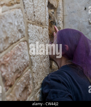 Christian pilgrim prays in the Fifth station of the Via Dolorosa during Good Friday in Jerusalem Israel - Stock Photo