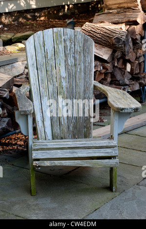 Old weathered wooden Adirondack style chair at Connecticut country home. - Stock Photo
