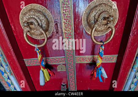 Detail of a traditional red door with decorated brass door fixtures at Namgyal Tsemo Monastery in Leh in Ladakh, India