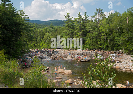 Swimmers on a hot summer afternoon at the lower falls of the Swift River in White Mountain National Forest. - Stock Photo