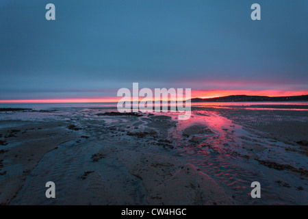 Sunrise over a beach in Wales showing red sky - Stock Photo
