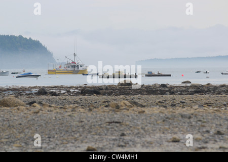 Typical maritime harbour with boats, fog, rocky shore and islands - Stock Photo