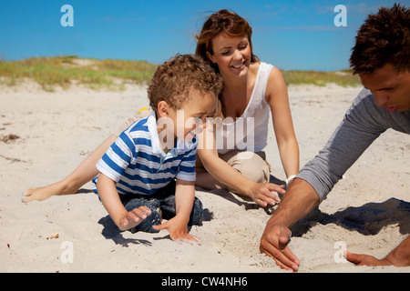 Young family enjoying the summer vacation on a sunny beach - Stock Photo