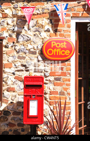 Royal mail red post box below a Post Office sign in a small Norfolk village - Stock Photo
