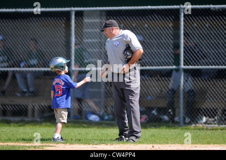 A bat boy provides an umpire with a baseball between innings during a high school baseball game. Illinois, USA. - Stock Photo