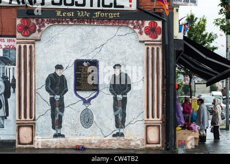 Local people at grocers with Political mural on Shankill road, Belfast in Northern Ireland. - Stock Photo