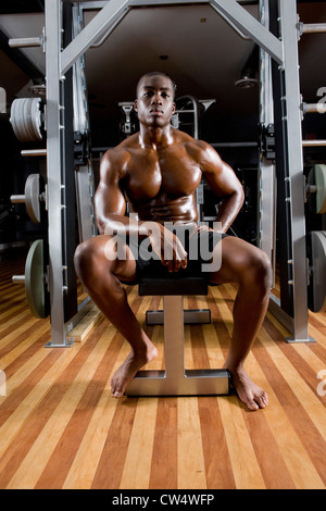 Portrait of a shirtless young man sitting in the gym - Stock Photo