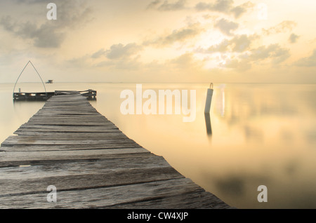 Warm sunset with old dock on caribean at Key Caulker, Belize - Stock Photo