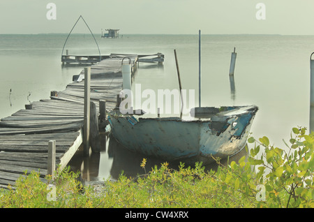 Calm day with dock and boat in ruins on Caribean at Caye Caulker, Belize - Stock Photo