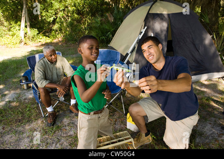 Mature man with his son and friend by tent at forest - Stock Photo