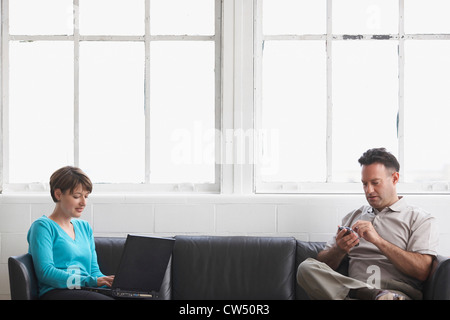 Businesswoman working on a laptop with a businessman using a PDA - Stock Photo