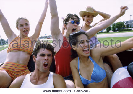 Group of young people sitting in a convertible car - Stock Photo