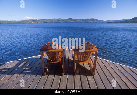 Two Adirondack chairs on a deck overlooking Lake George, NY - Stock Photo