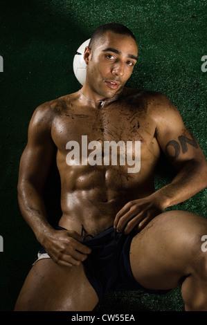 Muscular man lying on grass with soccer ball under head, studio shot - Stock Photo