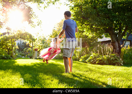 Dad and daughter playing in garden - Stock Photo