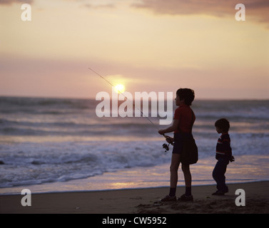 Silhouette of a boy fishing on the beach and his brother standing beside him, Vendee, France - Stock Photo