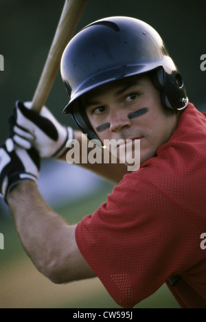Baseball player swinging a baseball bat - Stock Photo
