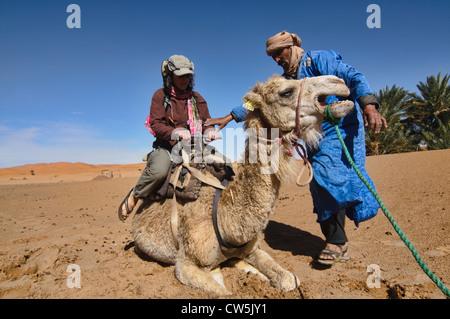 A Berber assists a tourist on a camel trek in the Sahara near Merzouga, Erg Chebbi, Morocco - Stock Photo