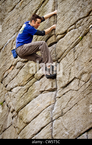 Tom Randall rock climbs a crack at Burbage in Sheffield near Stanage on the Peak District National Park Derbyshire, - Stock Photo