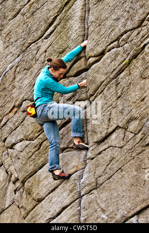A young women rock climbs a crack at Burbage, Sheffield, near Stanage in the Peak District National Park, England, - Stock Photo