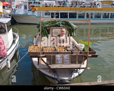 Woman selling potatoes and dill from her boat in the farmer´s marked i central Helsinki - Stock Photo