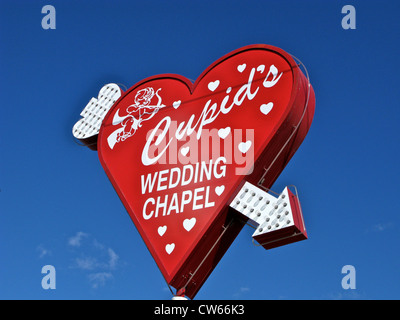 Red heart shape sign with neon arrow for Cupid's Wedding Chapel in Las Vegas Nevada USA - Stock Photo