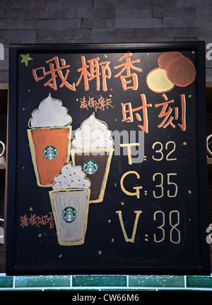 Sign in Chinese advertising Frappichino drinks at a Starbucks Coffee Shop in Beijing, China - Stock Photo