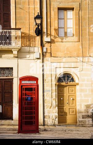 British telephone booth and traditional doors at Marsaxlokk, Malta - Stock Photo
