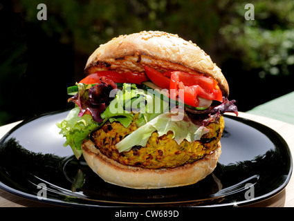 Vegetarian chickpea, sweetcorn and carrot burger with salad in a sesame seed bun, UK. - Stock Photo