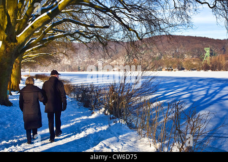 couple at frozen Baldeney Lake, in the background a pit frame of coal mine Carl Funcke, Germany, North Rhine-Westphalia, - Stock Photo