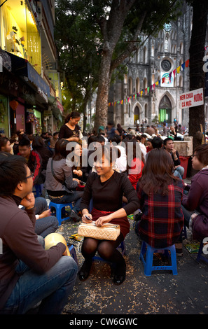 A crowd of people sitting in the streets front of an outdoor cafe with the old St. Joseph's Cathedral in the background. - Stock Photo