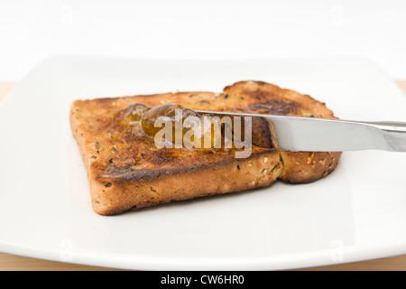 Spreading orange marmalade on slice of granary bread on white plate against white background - Stock Photo