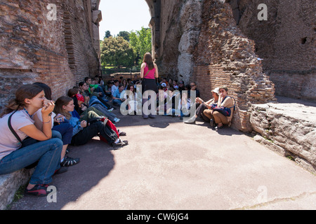 School class receiving instruction (in the shade at the colosseum rome Italy - Stock Photo