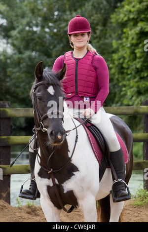 A young woman sat on a horse in a sand training ring outside on a sunny summer day - Stock Photo