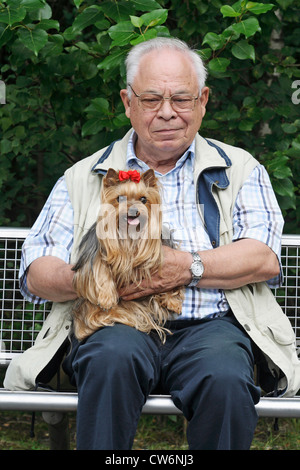 Yorkshire Terrier (Canis lupus f. familiaris), old man sitting on a bench with his 9 year old dog - Stock Photo
