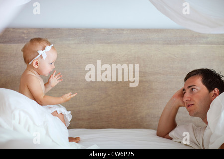 Young father and cute baby girl talking with each other in bed - Stock Photo