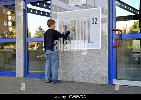 9 years old boy at a door plate of a multi-story building in Chorweiler, Germany, North Rhine-Westphalia, Cologne - Stock Photo