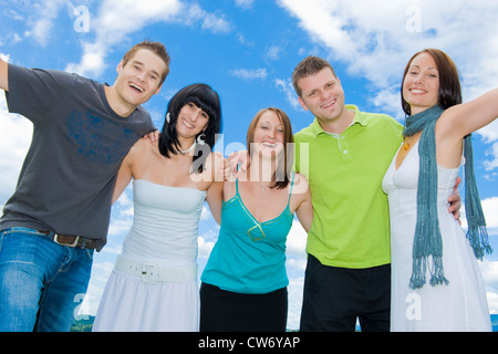 row of young people under open sky happily smiling while holding each other by the shoulders - Stock Photo