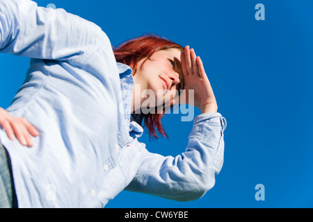 worms-eye view at a red-haired young woman in front of blue sky looking out with a hand shading the eyes - Stock Photo