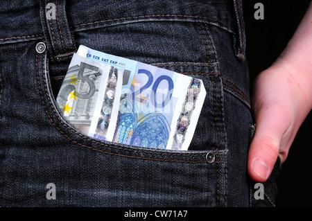 banknotes in trouser pocket, pocket money - Stock Photo