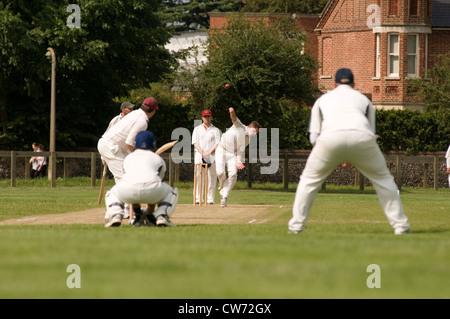 cricket match village green play playing players bat batsman bowler wicketkeeper wicket wickets grass green uk english - Stock Photo