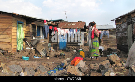 woman hanging up washing in the slums of the city of Goma, being called the 'burned quarter' ('quartier brul�') - Stock Photo
