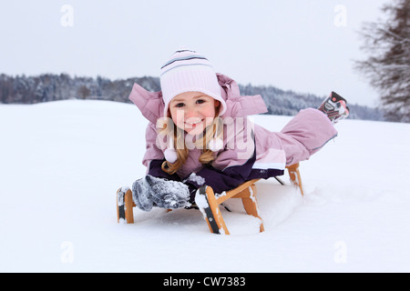little girl in a snow field lying on the belly on a wooden toboggan with a smile, Switzerland - Stock Photo